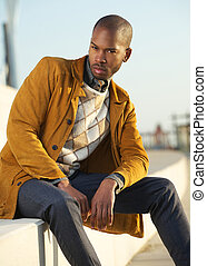 Handsome male fashion model sitting outdoors