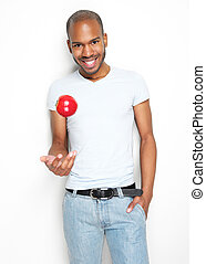 Healthy young man throwing up a red apple - Portrait of a...