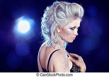 Hairstyle. Fashion Beauty Girl. Punk Style Woman with strasses on face, on a party lights background