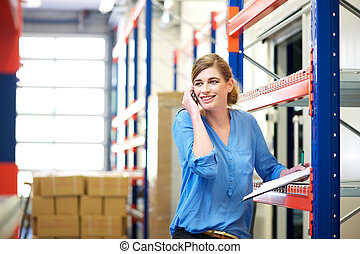 Female logistics worker controlling stock and talking on...