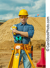 a contractor with theodolite on building place
