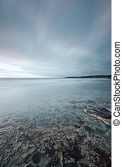 Submerged rocks, ocean and cloudy sky on bay beach -...