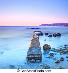 Concrete pier or jetty and rocks on a blue sea. Hills on background. Long exposure photography.