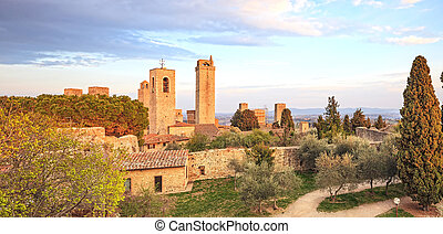 San Gimignano landmark medieval town. Sunset on towers and park with cypress and olive trees. Tuscany, Italy, Europe.