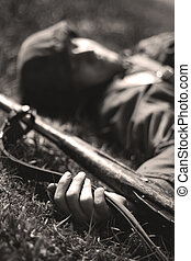 war - Dead soldier lying on the ground with a gun in his...