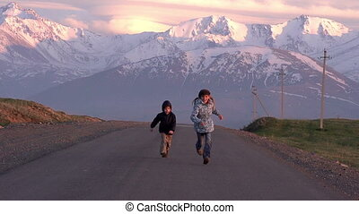 Children run into the setting Sun - Girl and boy running...