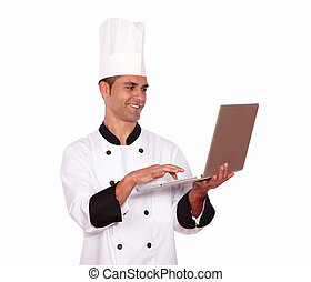 Handsome male in chef uniform working on computer - Portrait...