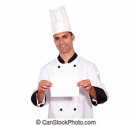 Charming male chef holding a white card while standing on...