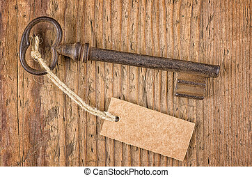 Old key with a tag on a wooden board