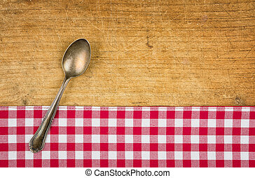 Silver spoon on a wooden board with a checkered tablecloth