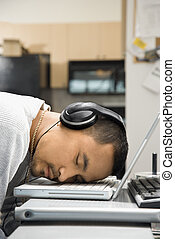 Man sleeping on laptop.