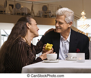 Man giving woman gift - Caucasian mature adult male giving...