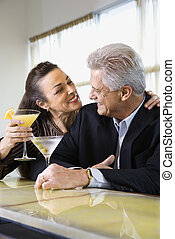Couple drinking at bar. - Caucasian mature adult male and...