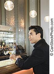 Man sitting at bar. - Prime adult Asian male sitting at bar.
