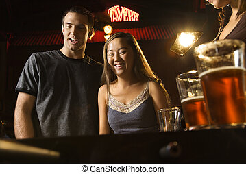 Couple at bar. - Young couple teamed up at foosball game in...
