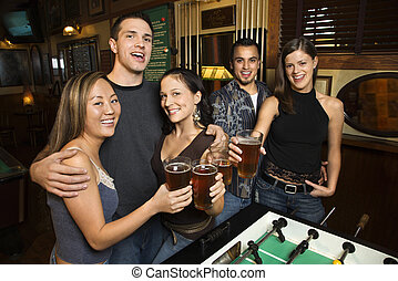 Group at pub - Portrait of group of young friends hanging...