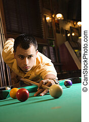 Man playing billiards - Young man concentrating while aiming...