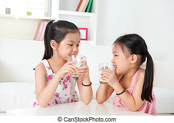 Children drinking milk Asian family at home Beautiful sister...