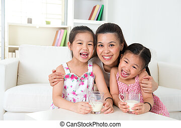 Mother and daughters drinking milk - Happy Asian mother and...