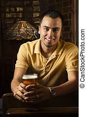 Man at bar smiling - Portrait of smiling young Hispanic man...