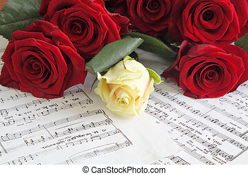 red and white roses on a sheet with notes