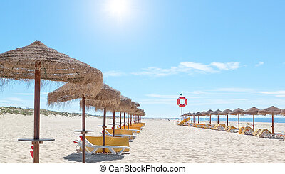 Beautiful sunny beach in Portugal with beach umbrellas and...