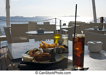 Delicious burger and a glass of cola on a table, with a beautiful sea view in the background