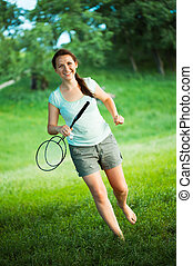 Smiling girl with a racket for a badminton in the park