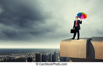 Businessman with umbrella atop of building