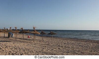 Romantic wide shot of the beach and parasols on Mallorca