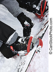 Person strapping on snowboard