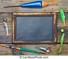 fishing gear and blackboard on wooden background