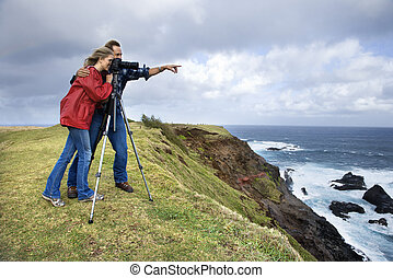 Couple using camera - Caucasian mid-adult couple pointing...