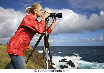 Woman taking pictures. - Caucasian mid-adult woman looking...