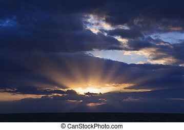 Sunbeams through clouds - Sunbeams coming through clouds at...