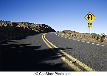 Road with sharp curve sign - Road and curve in road sign in...