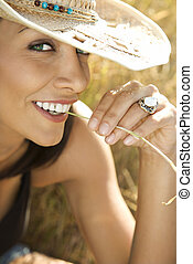 Woman chewing on straw. - Close-up of mid-adult Caucasian...
