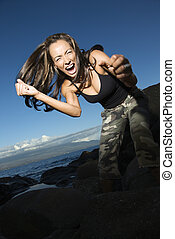 Woman gesturing. - Mid-adult Caucasian woman at rocky beach...