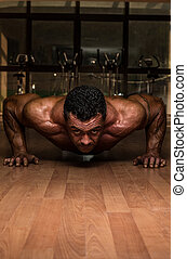 male bodybuilder doing push ups at the floor