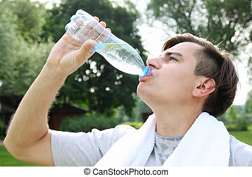 man drinks water - The young man drinks water from a bottle