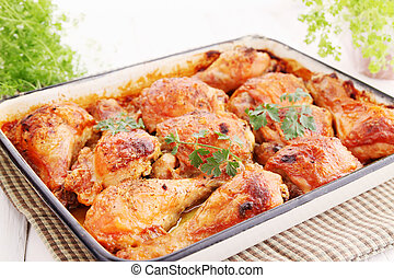 Baked chicken drumsticks on a baking tray