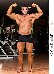 muscular body builder showing his front double biceps