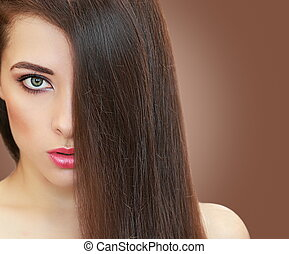 Beautiful girl with long hair on brown background. Closeup portrait