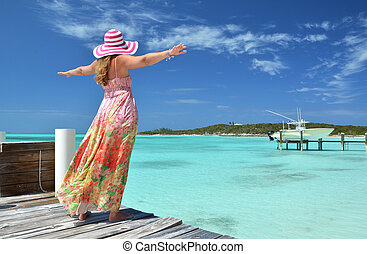Girl on the wooden jetty looking to the ocean. Exuma,...