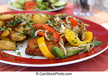 Schnitzel (German escalope) with fried peppers, onions and...