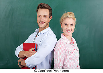 Smiling Man And Woman In Front Of Chalkboard