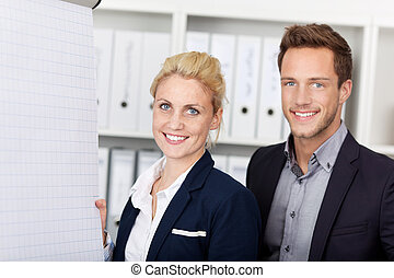 Smiling Businesspeople Working On Flipchart - Side view of...