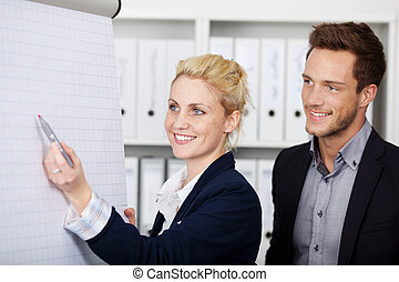 Businesspeople Working On Flipchart - Side view of two young...