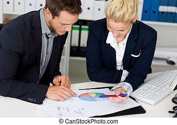 Smart Businessman And Woman Looking At Graphs - Portrait of...