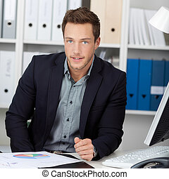 Smart Businessman With Graphs At Office Desk - Portrait of a...